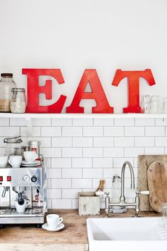 Bright red 'EAT' typography, timber chopping boards, white tile and stainless steel domestic espresso machine. Lovely kitchen nook.