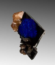 Azurite with Wulfenite 'An azurite crystal, sharp-edged with vibrant flashes of blue, has patches where the azurite has pseudomorphed to malachite' Tsumeb Mine, Namibia