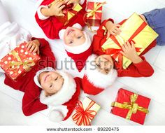 stock photo : Group of three children in Christmas hat with presents on floor