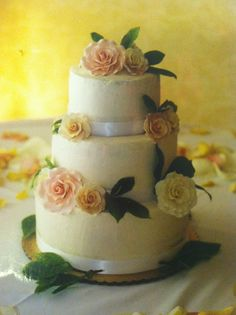 Small wedding cake with beautiful giant sugar roses in pale yellow and pink and white ribbon border