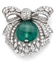 A DIAMOND, EMERALD, PLATINUM AND GOLD CLIP BROOCH, CIRCA 1930. Mounted in platinum and white gold with a stylish lace ribbon bow surmount, set with brilliant-cut diamonds and centering a large emerald.