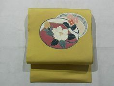 This is a Shioze Nagoya obi with a design of white camellia and flower arabesque on circle, which is dyed