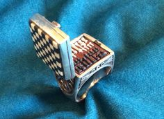 The tiny board, made from fossil ivory and ebony, flips up on wincy hinges to reveal 32 minuscule chess pieces. The ring itself is sterling silver, and there's only one of them, made by Arduosity, ...