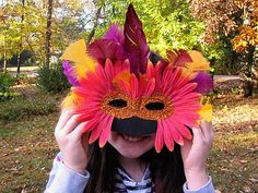 Make colorful feathered masquerade masks with glitter and flower petals with this surprisingly easy mask craft tutorial. #feathers # diy #thefeatherplace
