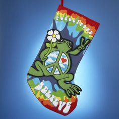 "$99.99-$124.99 Peace Frog Christmas Stockings Item #PF2107 Officially licensed merchandise  Vibrant retro colors and applique frog with peace sign, heart and flower decorate these bold stockings that read ""Peace Frogs BELIEVE"" Stocking comes ready-to-hang on red fabric loops  Dimensions: 19""H Materials: fabric  Pack includes 6 of the stocking shown"