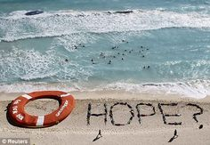 Message: Greenpeace activists stage a protest next to a giant life ring on a beach in Cancun, Mexico, after delegates agreed a climate change deal