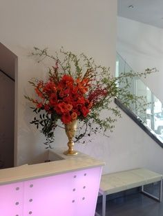 A GORGEOUS, free flowing, asymmetrical, arrangement! A unique arrangement that includes, various shades of orange flowers such as, roses, gladiolus, amaryllis, Satsuma branches (yes! the fruit!) and an assortment of local foliage, all in a large gold vase. This arrangement was displayed at a modern art museum, Martine Chaisson Gallery, located at 727 Camp St., in New Orleans Art District (Warehouse District).
