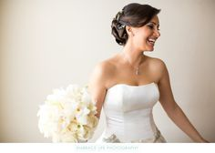 Embrace Life Photography - Riviera Country Club Wedding Photographer: Candid photograph of a beautiful, laughing Persian bride wearing her brunette hair in a formal updo decorated with jeweled, floral design clips. Her diamond and white gold jewelry perfectly compliments the trim on the bodice of her strapless wedding gown as does her lovely white bouquet of calla lily, orchids and roses. The Riviera Country Club is located in Pacific Palisades, CA. Phone: (310) 454-6591. Website…