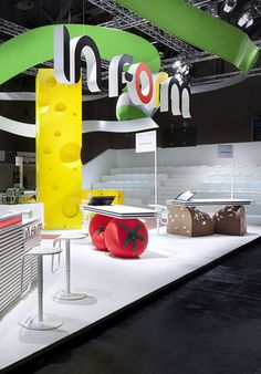 The backoffice in milk cartons, partner counters made of fruit, vegetables, bread and sausage, the activity area with an oversized tower of cheese, and above it all a freshly peeled apple and the initiative's logo. #booth #stand #exhibit