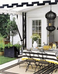 Durable, Greek key-patterned outdoor rugs soften the concrete patio and help define the dining area. And a row of patio doors provides natural light and a view to the yard, while also opening up the small space.