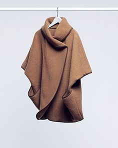 Cape in a felted wool blend. Cap sleeves, wrap-style front with snap fasteners at top, and front pockets.