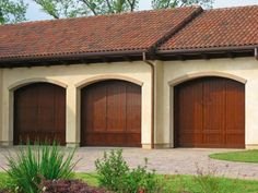 Three car garage. Wooden doors and cool tiled roof. Love the landscaping and cobbled driveway too.