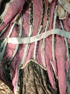 Charles Frederick WORTH, manteau de robe en velours façonné, vers 1880. Velours de soie ciselé, frisé et coupé, vert- olive au décor de boutons de rose crème. Veste ¾ à manches longues avec corsage intégré boutonné en taffetas ivoire et jabot de dentelle Valenciennes mécanique (bel état). Griffe tissée en brun sur fond crème sur le ruban de taille: «Worth -Paris»