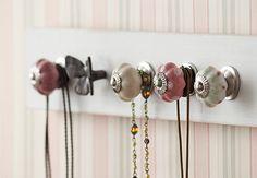 Os puxadores de porcelana com pegada romântica viraram penduradores para organizar bijuterias. O papel de parede com listas em tons de rosa pastel completa o visual candy