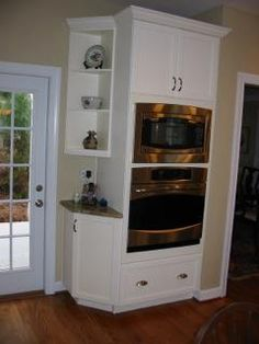 We replaced the double patio door with a single door to make room for the tall cabinet that now houses the microwave and oven. This cabinet was custom made to the height specified by the homeowner, and it includes an ample-sized drawer for storage. We took advantage of the leftover space by adding a small angled cabinet with open shelving above.