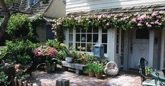 English Cottage Garden.  I would love to have flowers under the eves like this.