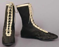 Black sateen-covered canvas bathing shoes, American, 1915-1918. The shoes are trimmed with a band of white leather around the top and down the sides of front openings, laced with round white cotton lacing, and have canvas soles.
