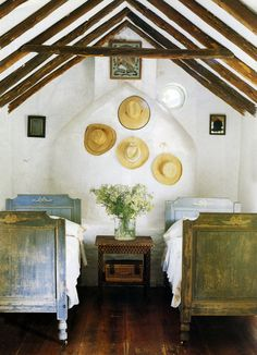 I love the shape of this room the beds and the flowers. I would never put those hats on the wall, and those pictures have got to go..... But the room, the ceiling, the beds, the flowers...... possibilities.