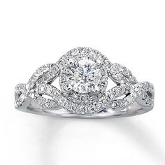 Take her breath away with this stunning engagement ring. A luminous round diamond is surrounded by numerous diamonds that are also featured in elegant twists of 14K white gold. This fine jewelry ring has a total diamond weight of one carat. Diamond Total Carat Weight may range from .95 - 1.11 carats.