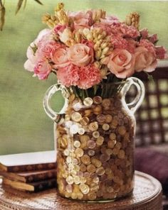 Simply Lovely and Creative Decor idea. Buttons in glass jar displaying a bouquet of flowers.