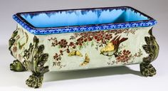 French parcel gilt majolica jardinière by Theodore Deck, late 19th century, of rectangular form having a turquoise interior and a gadrooned rim, above a body decorated in the Japonesque taste with gilt birds and butterflies and burgundy cherry blossoms, the whole rising on olive green paw feet with acanthus knees, the underside having the mark for Theodore Deck, an impressed TH as well as a bas relief bust in an oval.