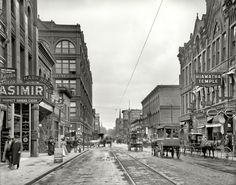 """St. Paul, Minnesota, c. 1908. """"Wabasha Street."""" Abundantly equipped with fraternal organization, painless dental parlors, purveyors of cigars and prosthetic eyeballs, optician-jeweler (with the 8:17 clock-sign) and """"Business Men's Lunch (And 2 Beers)"""" for 15 cents."""