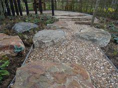 Aanleg festivaltuin 'Bal Populaire' in De Tuinen van Appeltern - Grauwacke keien als hindernis in een schelpenpad. Op de achtergrond zijn eiken stammen in de halfverharding verwerkt als hindernis.