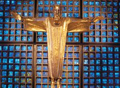 Berlin's Top 10 : Kaiser-Wilhelm-Gedächtnis-Kirche - Main Altar    The golden figure of Christ created by Karl Hemmeter is suspended above the modern main altar in the new church. In the evening light, the windows behind the altar glow an overwhelming dark blue.
