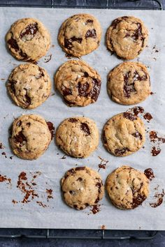chewy vegan tahini chocolate chip cookies on parchment over a cooling rack