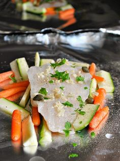 Baked cod with carrots, zucchini, lemon and capers in a foil packet.