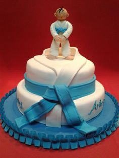 """Two-tier gi with figure on top Cakes can be 6"""" (serves 10) on 8"""" (serves 24) or 9"""" (serves 32). Price is $2.50/serving $85 or $105 + tax"""