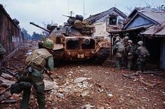 U.S. Marines congregate in back of tank on a residential street. The tank is firing over an outer wall of the citadel. Hue, February 13th, 1968.