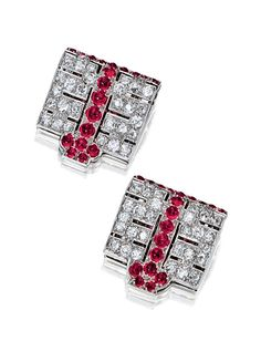 PAIR OF RUBY AND DIAMOND CLIPS, CARTIER, CIRCA 1925.   Each of geometric design, set with circular- and brilliant-cut diamonds, decorated with cabochon rubies,  signed Cartier and numbered.