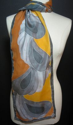 Platinum silver and charcoal deco style feathers float down this beautiful silk scarf against shades of golden ochre. The unique color combination is so striking and the bold graphic art deco style makes a fantastic fashion statement and pop of color to your wardrobe. Goes great with gold or silver accessories, and will dress up any outfit! The light weight crepe de chine silk is opaque, has a pretty sheen, and is light enough to float in the breeze.    Measures 11x58    Want to see more…