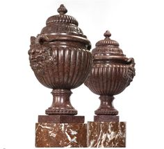 Property from the Collections of Lily & Edmond J. Safra - A rare pair of Louis XV carved porphyry lidded vases, circa 1760,    on later veined marble pedestals, each with gadrooned and stepped domed covers carved with acanthus and mounted with knob finials, the gadrooned bodies carved with satyr masks issuing fruiting vines, raised on a spreading plain socle with rope-twist base, on a square plinth. height of vases 36 in.; height of pedestals 55 3/4 in. 91.5 cm; 142 cm