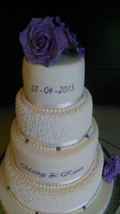 Bruidstaart met cornelli lace op 4 lagen taart met gumpaste suikerbloemen. De namen en datum zijn erop geschilderd