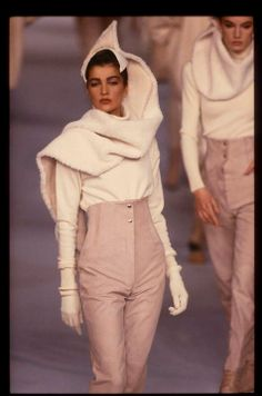 Sculptural shawl in white, white slim fitting turtleneck jumper with a buttoned super high waisted pale nude pink coloured pair of trousers by Claude Montana, Fall 1987