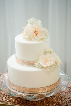 Beautiful white cake with blush roses and rose gold sequined ribbon detail on a pretty frilly glass stand.
