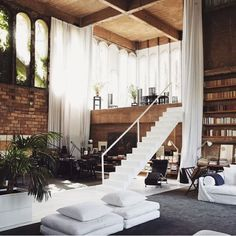 Wow! I want to dine on that mezzanine floor with those enormous dreamy curtains. That ceiling, the brick, the arched windows and the bookshelves! Simple, rustic, super clever loft conversion...EMMACESKI ♡
