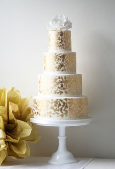 Brides.com: . A four-tiered white wedding cake with gold-fleck details and a floral topper, from Ivory & Rose Cake Company.