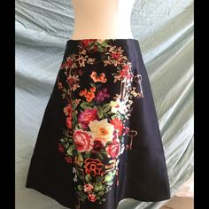 Black A-line satin skirt with Floral/ Keys Design This skirt is a vibrant black A-line style with the famous floral/ skeleton key design that has been popularized by Italian fashion runways.  Lined satin skirt falls below the knee.  Size Medium but fits like a Small.  Hidden side zipper. Skirts Midi