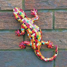 Mosaic resin lizard  Orange coloured design  Frost & weather resistant  Comes complete with hook on the back to mount on a wall or fence  Size 24cm long, 12cm wide  Ideal to brighten up a dull wall or fence in the garden £24.99