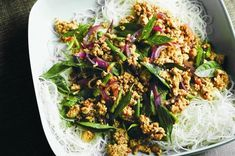 Thai pork stir-fry - 1 T peanut oil, 1 red onion, 1 T finely chopped lemongrass, 1 long red chilli, 1 T finely chopped ginger, 2 garlic cloves, 500g pork mince, 2 T gluten-free massaman curry paste, 100g green beans, 1 1/2 T fish sauce, 2 T lime juice, 1 T brown sugar, 1 cup Thai basil leaves, cooked thin rice noodles