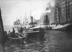 0954049 Hafenanlage des Altonaer Hafens - hohe Speichergebäude und Lagerhäuser stehen an der Wasserseite von der aus direkt von den Schiffen die Ladung gelöscht werden kann. An einer langen Reihe von Duckdalben aus Baumstämmen / Tannenstämmen haben Schiffe festgemacht. Im Vordergrund re. ein Ruderboot aus Holz, die Ruder liegen im Boot. Zwei Hafenarbeiter blicken zum heran fahrenden Schlepper, der eine mit Säcken beladene Schute zieht.