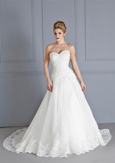 This classic A-line organza gown is truly beautiful. Figure-flattering with its pleated bodice and asymmetric lace applique detail. Fine lace decorates Dublin's hem and skirt as well finishing touched including a sweetheart neckline and zip & button back fastening.