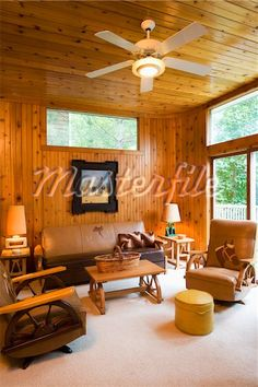 SITTING AREAS: Knotty pine walls and ceiling, western theme, wagon wheel furniture with leather cushions and horses, Stock Photos