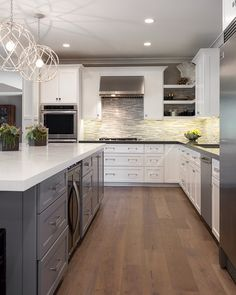"White cabinets with grey Caesar stone countertops. Opposite colors on the island make a good contrast. ""Driftwood"" wood floors."