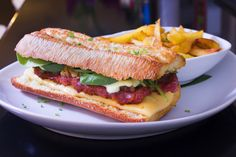 Pepito Catalán: Pan chapata, butifarra de payés, cebolla caramelizada, queso gouda, lechuga y salsa Anauco.