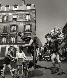 Enfants aux patins à roulettes rue de Ménilmontant | Robert Doisneau