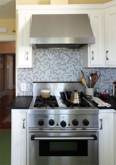 gray tile backsplash, black counter with the white cabinets